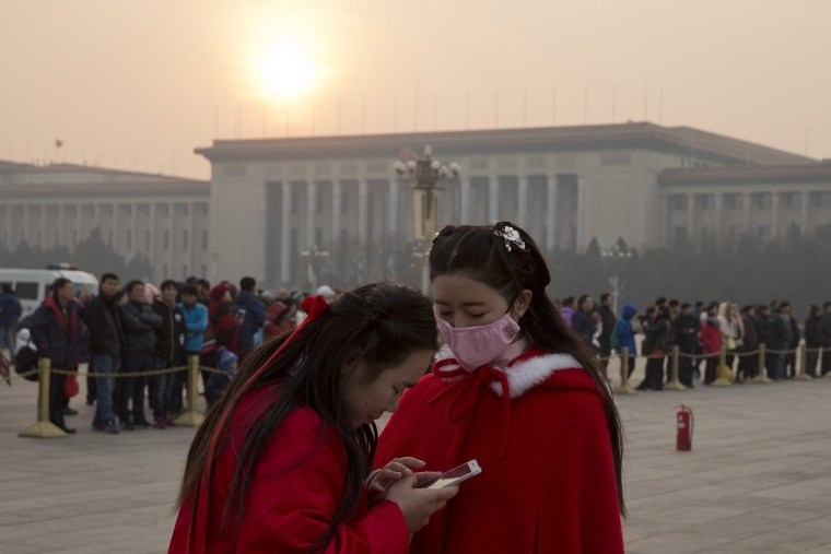 A Chinese woman wears a mask as she visits Tiananmen Square in Beijing, China, Dec. 19, 2015. (Photo by Ng Han Guan/AP)