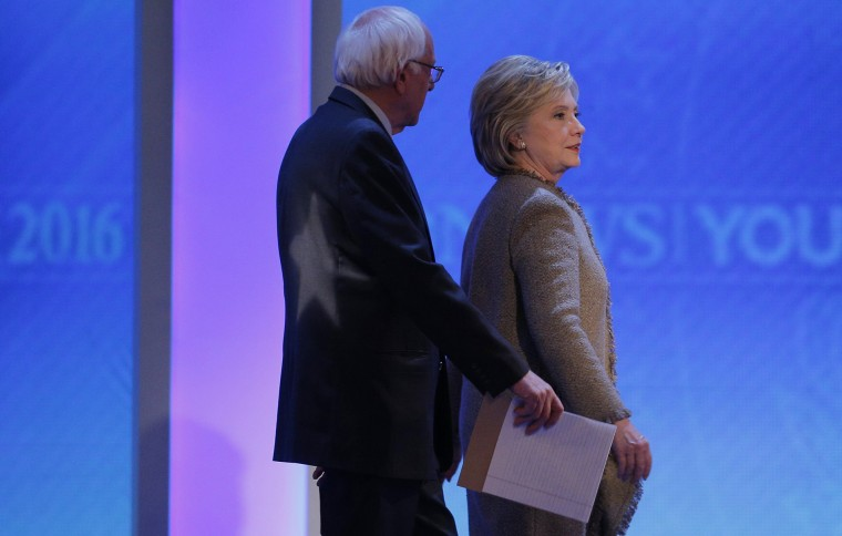 Democratic presidential candidates Bernie Sanders and Hillary Clinton talk as they return to the stage together at the end of a commercial break at presidential debate, Manchester, N.H. Dec. 19, 2015. (Photo by Brian Snyder/Reuters)