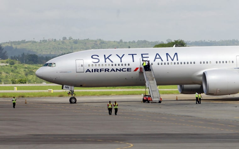 Airport workers are seen near the Air France Boeing 777 aircraft that made an emergency landing is pictured at Moi International Airport in Kenya's coastal city of Mombasa, Dec. 20, 2015. (Photo by Joseph Okanga/Reuters)
