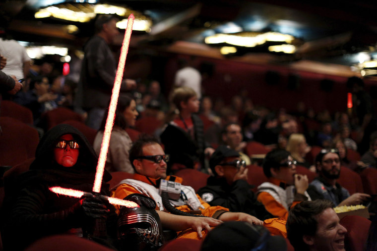 """Moviegoers Dawn and Daniel Bright sit before the first showing of the movie """"Star Wars: The Force Awakens"""" at the TCL Chinese Theatre in Hollywood, Calif., Dec. 17, 2015. (Photo by Mario Anzuoni/Reuters)"""