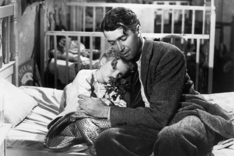 Actor James Stewart as George Bailey, hugs actor Karolyn Grimes, who plays Zuzu his daughter, in a still from director Frank Capra's Christmas classic film, 'It's a Wonderful Life'. (Photo by Hulton Archive/Getty)
