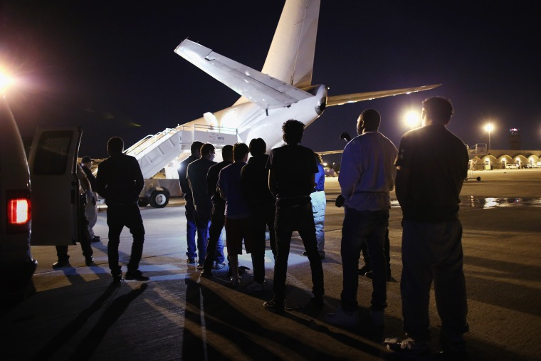 Undocumented immigrants wait to be loaded onto an Immigration and Customs Enforcement (ICE) charter jet early on Oct. 15, 2015 in Mesa, Ariz. (Photo by John Moore/Getty)