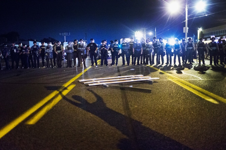 Police stand guard as demonstrators, marking the one-year anniversary of the shooting of Michael Brown, protest along West Florrisant Street on Aug. 10, 2015 in Ferguson, Mo. (Photo by Scott Olson/Getty)
