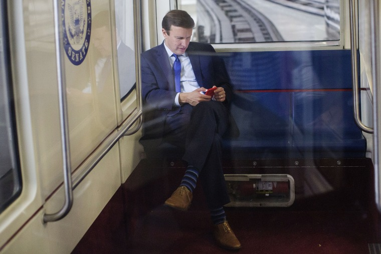 Sen. Chris Murphy, D-Conn., uses his cell phone as he rides the Senate subway in Washington, D.C., Dec. 1, 2015. (Photo By Al Drago/CQ Roll Call/AP)