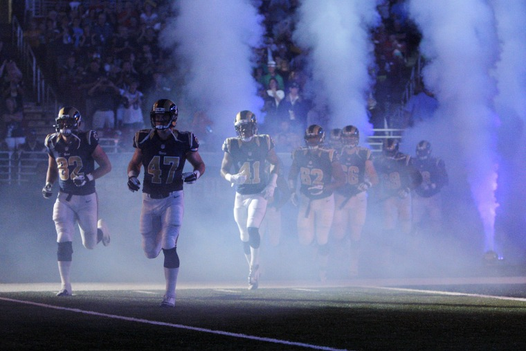 In this Aug. 16, 2014 file photo, members of the St. Louis Rams run onto the field before the start of an NFL football game in St. Louis, Mo. (Photo by Scott Kane/AP)