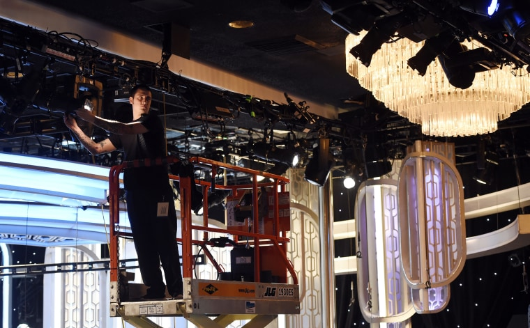 Crew member Chris Lopez adjusts lights in the ballroom during the 73rd Annual Golden Globe Awards Preview Day at the Beverly Hilton, Jan. 7, 2016, in Beverly Hills, Calif. (Photo by Chris Pizzello/Invision/AP)