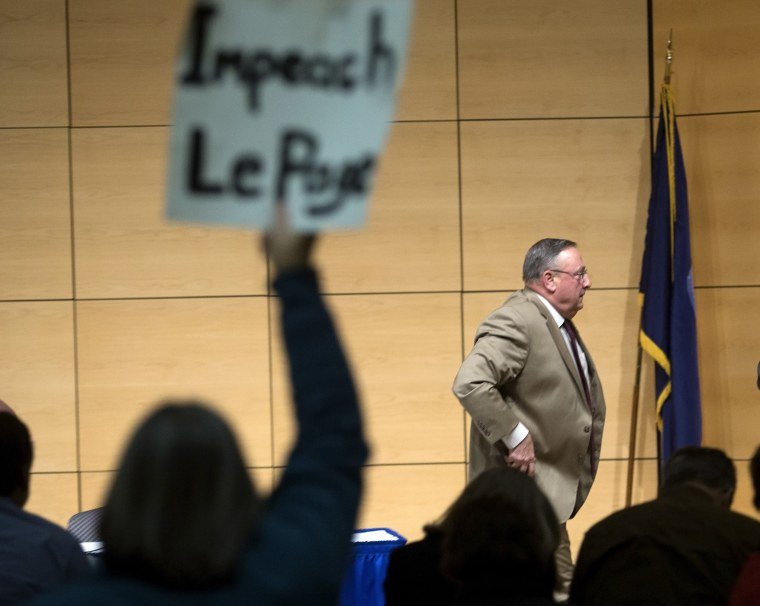 Gov. Paul LePage brings his town hall tour to Portland, speaking at the Abromson Center at the University of Southern Maine on Dec. 8, 2015. An audience member holds up a sign as LePage leaves the room. (Photo by Derek Davis/Portland Press Herald/Getty)