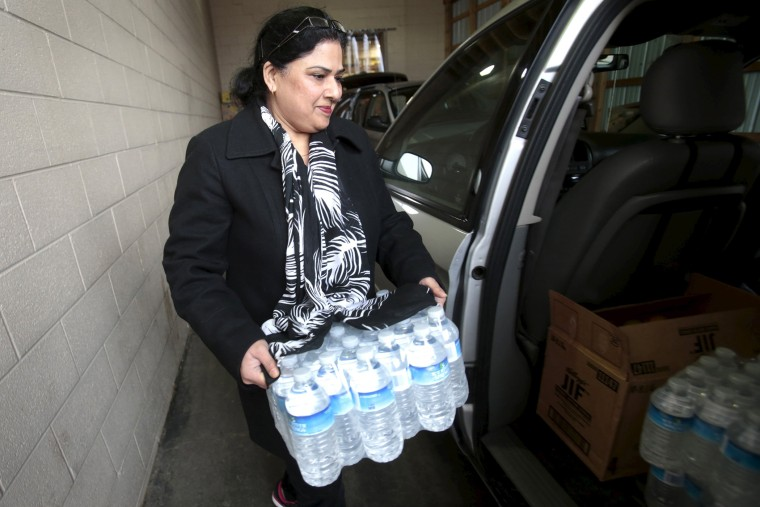 Food Pantry volunteer Asia loads bottled water into a vehicle at the Food Bank of Eastern Michigan's warehouse that will be distributed to the public, after elevated lead levels were found in the city's water, in Flint, Michigan, December 16, 2015.