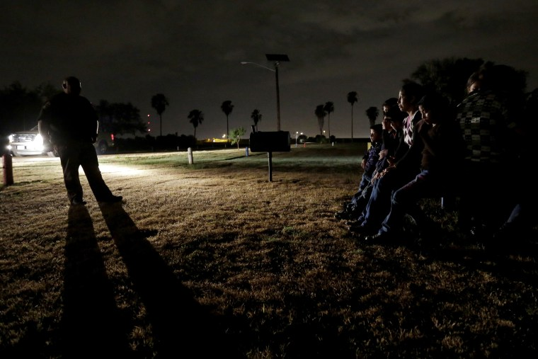 In this June 25, 2014, file photo, a group of immigrants from Honduras and El Salvador, who crossed the U.S.-Mexico border illegally, are stopped in Granjeno, Texas. (Photo by Eric Gay/AP)