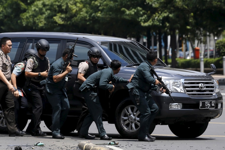 Indonesian police hold rifles while walking behind a car for protection in Jakarta on Jan. 14, 2016. (Photo by Beawiharta Beawiharta/Reuters)