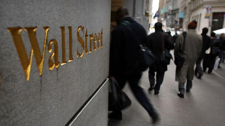 People walk down Wall Street in New York City. (Photo by Spencer Platt/Getty)
