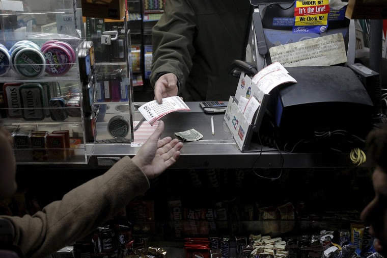 A customer purchases a Powerball lottery tickets at a news stand on Jan. 13, 2016. (Photo by Brendan McDermid/Reuters)