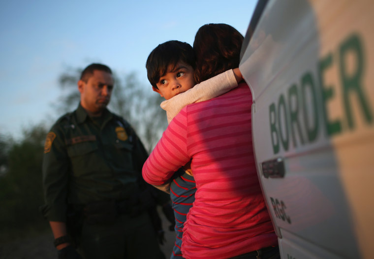 A one-year-old from El Salvador clings to his mother after they turned themselves in to Border Patrol agents after entering the country illegally on Dec. 7, 2015 near Rio Grande City, Texas. (Photo by John Moore/Getty)