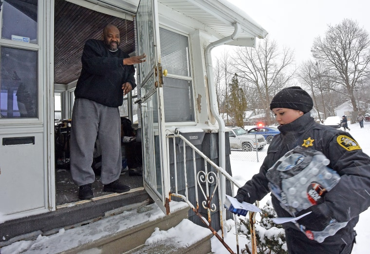 Samuel Smith receives a case of bottled water and a new water filter in Flint, Mich., as volunteers, Michigan State Police and Gennessee County Sheriff's Deputies deliver to residents, Jan 12, 2016. (Photo by Dale G. Young/The Detroit News/AP)