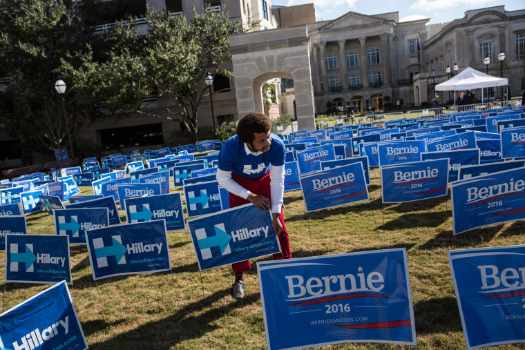 A man places signs supporting Hillary Clinton for the democratic presidential nominee outside the Gaillar Center prior to tonight's Democratic debate on Jan. 17, 2016 in Charleston, S.C. (Photo by Andrew Burton/Getty)