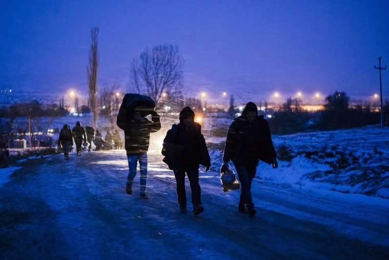 Migrants and refugees walk on a snow covered street after crossing the Macedonian border into Serbia near the village of Miratovac on Jan. 17, 2016. (Photo by Dimitar Dilkoff/AFP/Getty)