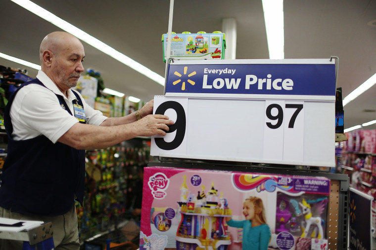 Jesus Gutierrez puts a low price dollar sign together at a Walmart store as they prepare for Black Friday shoppers on Nov. 24, 2015 in Miami, Fla. (Photo by Joe Raedle/Getty)