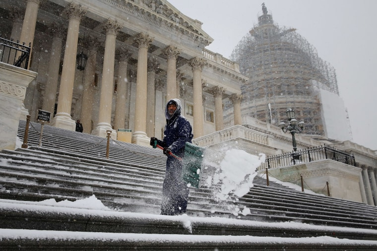 Clearing a path for Congress, an employee of the Architect of the Capitol shovel snow off the steps of the U.S. House of Representatives as more snow continues to fall on Jan. 6, 2015 in Washington, DC. (Photo by Chip Somodevilla/Getty)