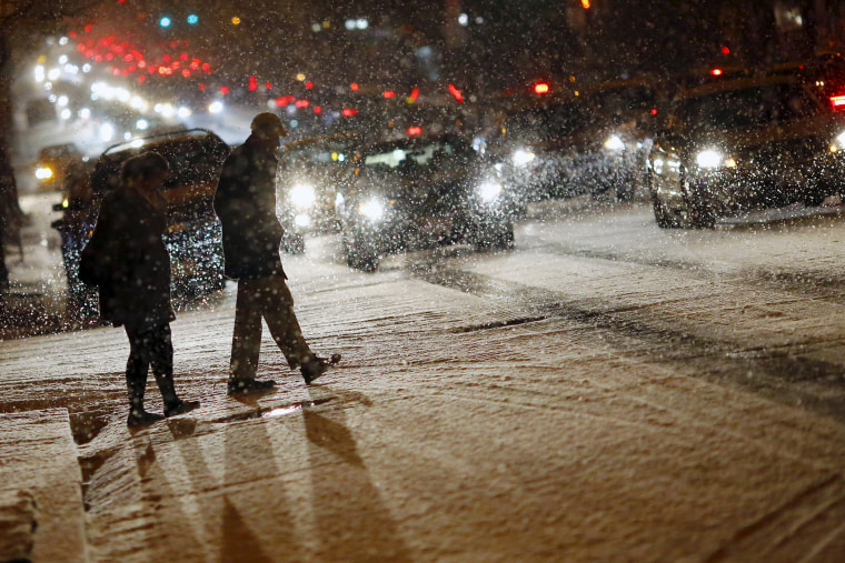 People cross a street as it snows in Washington, Jan. 20, 2016. (Photo by Carlos Barria/Reuters)