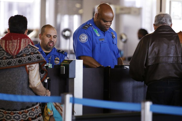 In this Nov. 25, 2015 file photo, TSA agents check travelers' identifications at O'Hare International Airport in Chicago. (Photo by Nam Y. Huh/AP)