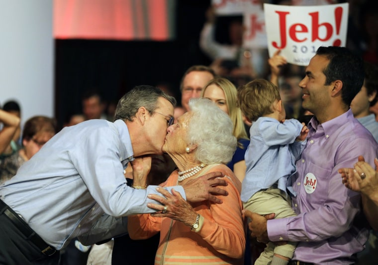 Former Florida Gov. Jeb Bush, left, kisses his mother Barbara as his son George, right, watches as he takes the stage to formally join the race for president with a speech at Miami Dade College, June 15, 2015, in Miami. (Photo by David Goldman/AP)