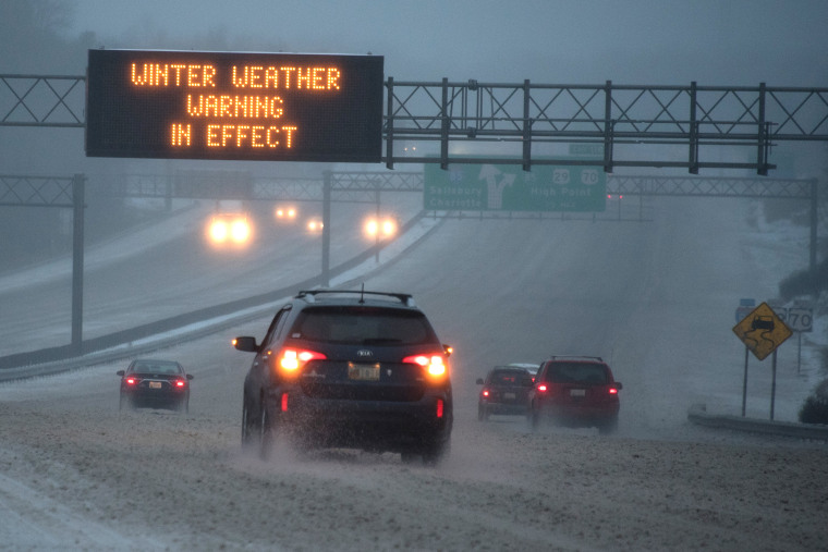 Vehicles move along Interstate 85 as an overhead sign indicates 'WINTER WEATHER WARNING IN EFFECT' during a winter storm on Jan. 22, 2016 in Greensboro, N.C. (Photo by Lance King/Getty)