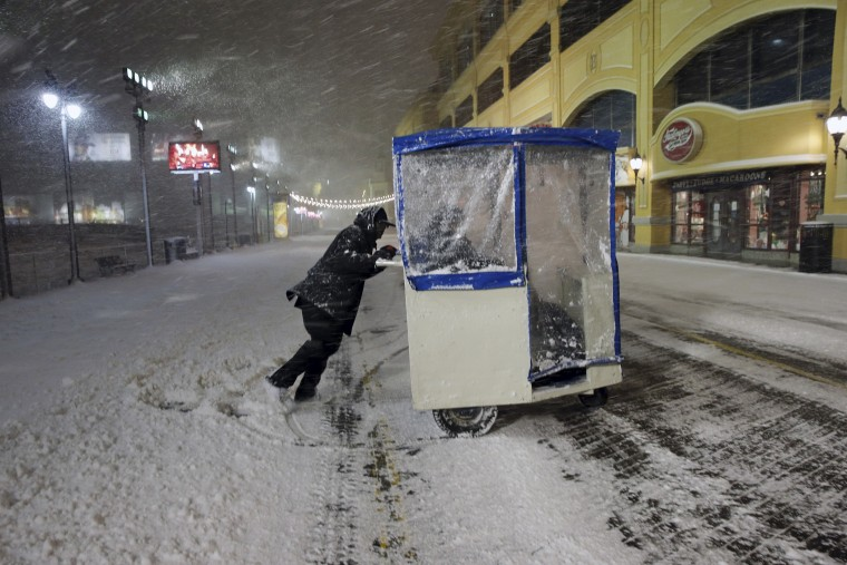 A man maneuvers his Push cart with passengers during a snowstorm early Jan. 23, 2016, on the Atlantic City Boardwalk. (Photo by Mel Evans/AP)