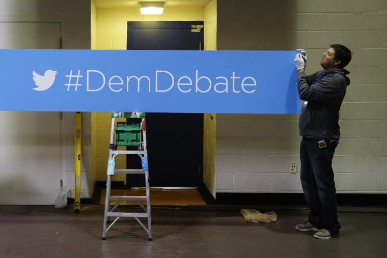 A sign for the Democratic debate hashtag is hung in the media filing center before the Nov. 13, 2015 Democratic Presidential Debate in Des Moines, Iowa. (Photo by Charlie Neibergall/AP)