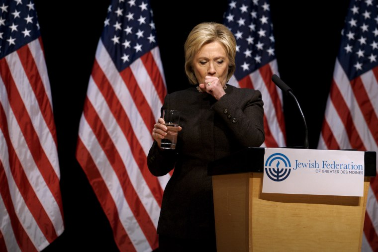 Democratic presidential candidate Hillary Clinton holds up a glass of water as she struggles to contain a coughing fit at the Jewish Federation of Greater Des Moines, Iowa, Jan. 25, 2016. (Photo by Rick Wilking/Reuters)