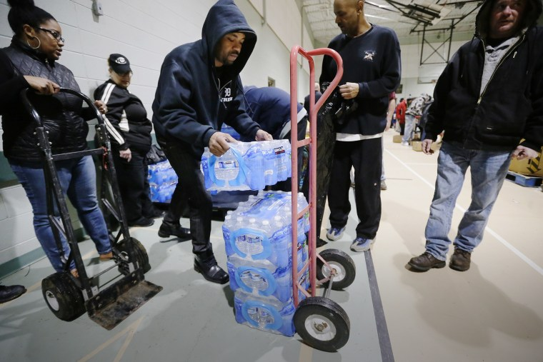 Will Burnett helps load a cart with bottled water at the Salvation Army Flint Beecher Corps Community Center in Flint, Mich., Jan. 26, 2016. (Photo by Carlos Osorio/AP)