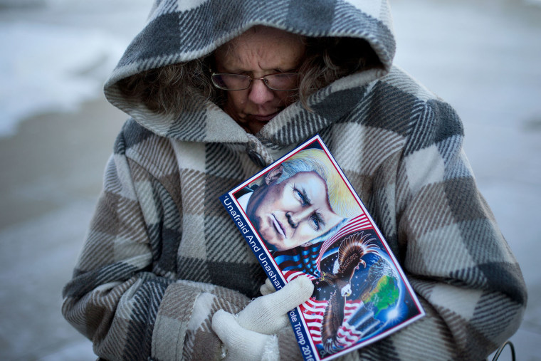 Debbie Heinick shivers while waiting in line to attend a rally for Republican presidential candidate Donald Trump, Jan. 12, 2016, in Cedar Falls, Ia. (Photo by Jae C. Hong/AP)