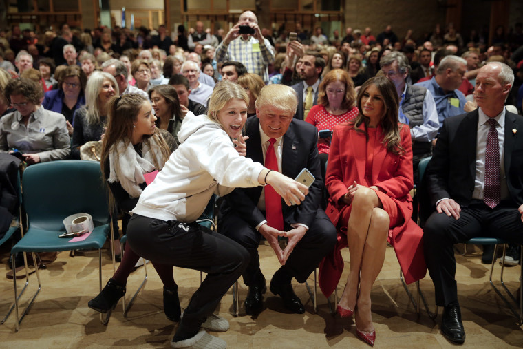 Republican presidential candidate Donald Trump, accompanied with wife, Melania, pauses for a selfie while visiting Saint Francis of Assisi Church, a caucus site, Feb. 1, 2016, in West Des Moines, Iowa. (Photo by Jae C. Hong/AP)