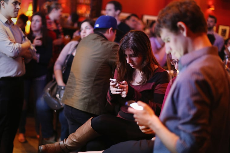 Young adults split their attention between a televised Democratic debate and using their smart phones during a watch party in Washington, DC., Oct. 13, 2015. (Photo by Chip Somodevilla/Getty)