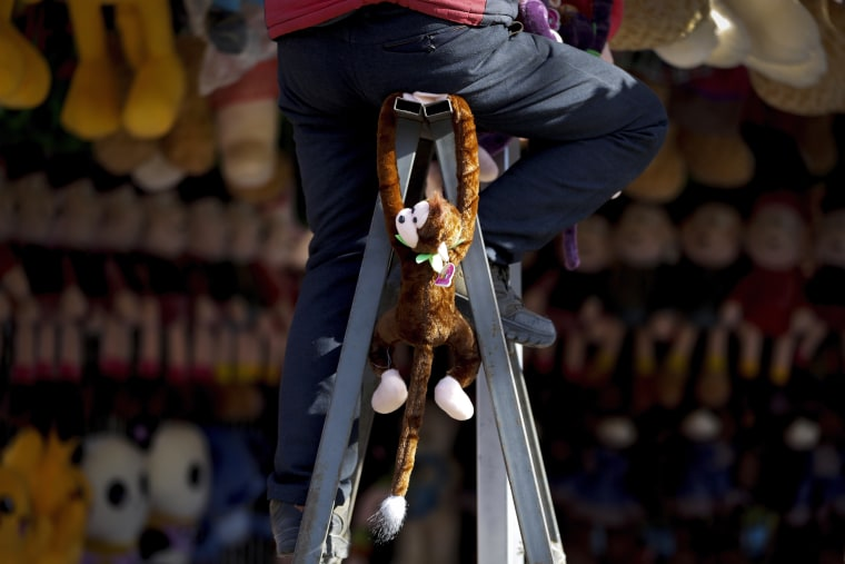 A monkey soft toy is hanged on a ladder as a worker sets up a store for a temple fair ahead of Chinese Lunar New Year at Ditan Park in Beijing, Feb. 6, 2016. Parks and temples across the capital city are gear up for the Lunar New Year celebrations on Feb. 8 this year which marks the Year of Monkey on the Chinese zodiac.