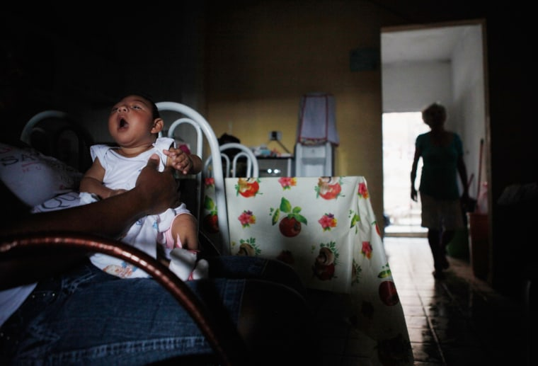 Alice Vitoria Gomes Bezerra, 3-months-old, who has microcephaly, is held by her mother Nadja Cristina Gomes Bezerra on Jan. 31, 2016 in Recife, Brazil. (Photo by Mario Tama/Getty)