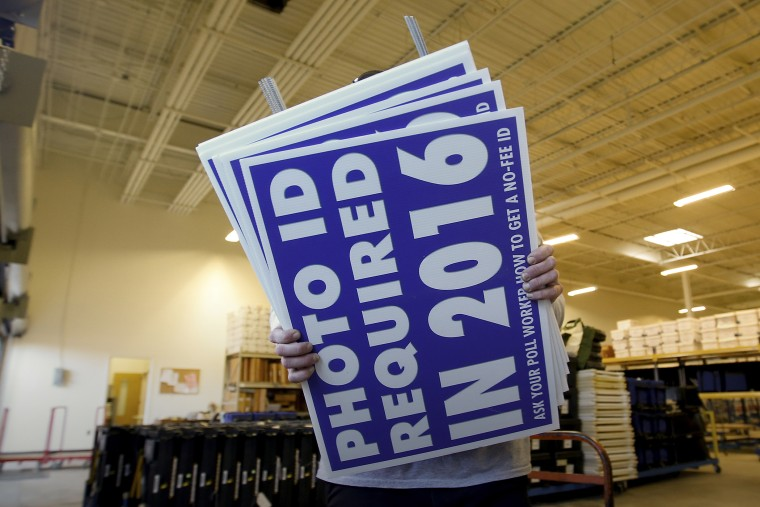 A worker carries signs about a voter ID law that went into effect in 2016 at the Mecklenburg County Board of Elections warehouse in Charlotte, N.C., Nov. 3, 2014. (Photo by Chris Keane/Reuters/Corbis)