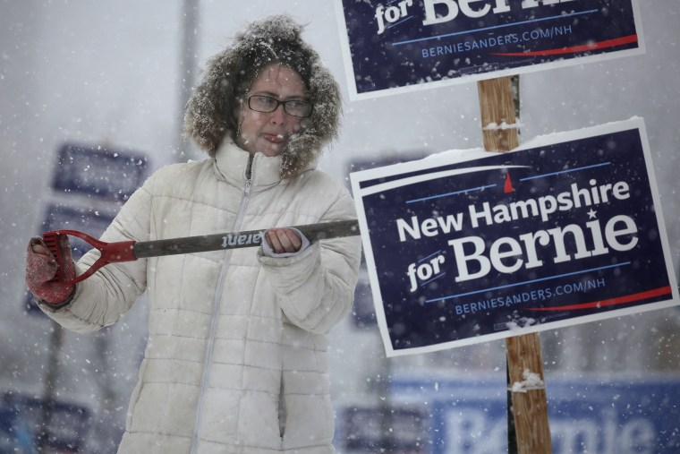 A worker uses a shovel to wipe snow off of an election sign in Manchester, N.H., Feb. 5, 2016. (Photo by Carlo Allegri/Reuters)