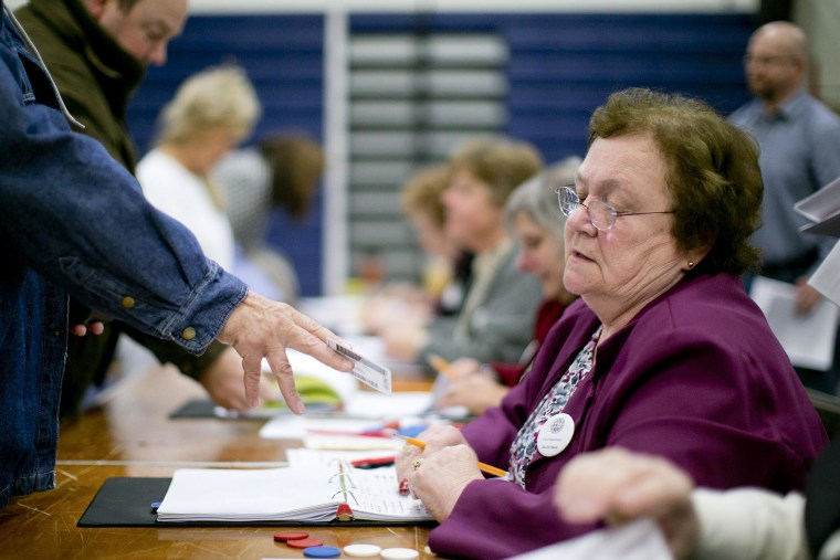 Norma Boyce checks voter identification at a polling station in Manchester, N.H., Nov. 6, 2012. (Photo by Andrew Harrer/Bloomberg/Getty)