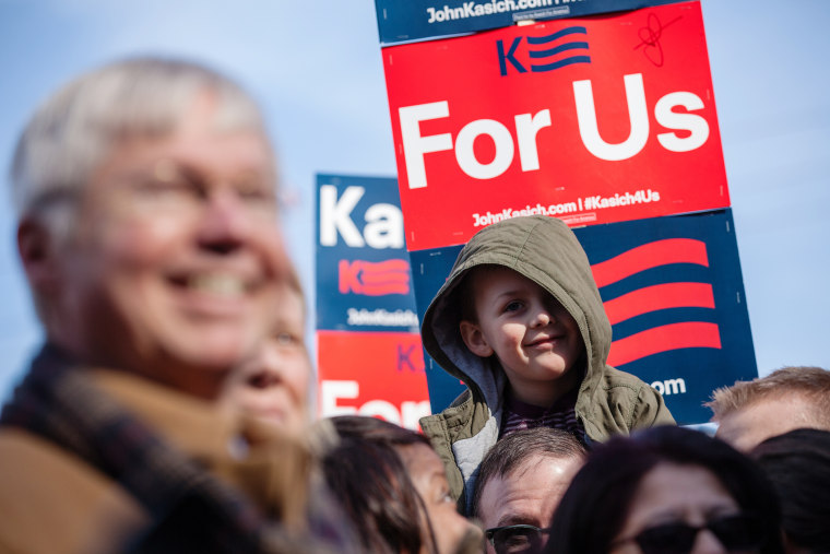 A child listens to Republican presidential candidate John Kasich speak to campaign workers and volunteers outside his campaign headquarters in Manchester, N.H., Feb. 6, 2016. (Photo by Matthew Cavanaugh/Getty)