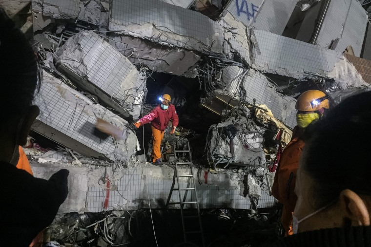 A rescue worker (C) discards an object as he searches through rubble for belongings for relatives from the remains of a building which collapsed. (Photo by Anthony Wallace/AFP/Getty)