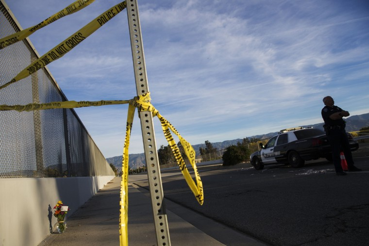A San Bernardino police officer stands on the perimeter as crime scene tape and flowers rest near the Inland Regional Center on Dec. 3, 2015 in San Bernardino, Calif. (Photo by Patrick T. Fallon/AFP/Getty)