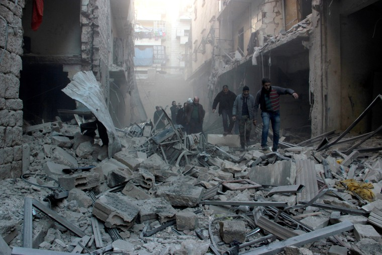 People walk past the rubbles as Russian airstrikes pound residential areas at opposition controlled Salihin neighborhood of Aleppo, Syria on Feb. 8, 2016. (Photo by Ibrahim Ebu Leys/Anadolu Agency/Getty)
