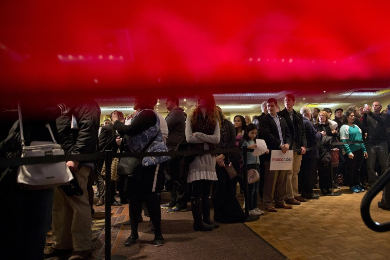 Seen from behind a American flag, supporters of Sen. Marco Rubio, R-Fla. gather for his primary night rally at the Radisson Hotel in Manchester, N.H., Feb. 9, 2016. (Photo by Jacquelyn Martin/AP)
