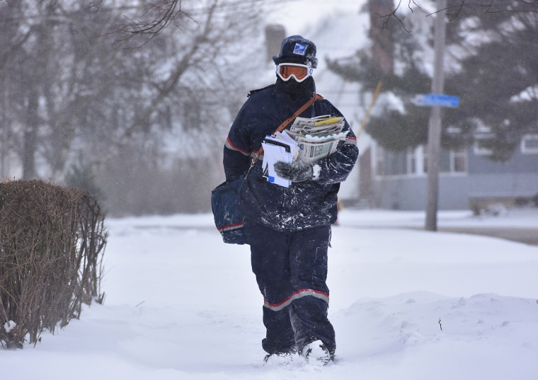 Jake Cote, a carrier with the United States Postal Service, delivers mail along Sunset Avenue, Feb. 11, 2016, in Utica, N.Y. (Photo by Mark DiOrio/Observer-Dispatch/AP)