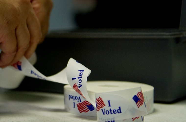 """A voter peels off an """"I Voted"""" sticker after casting her ballot at a polling station. (Photo by Jim Watson/AFP/Getty)"""