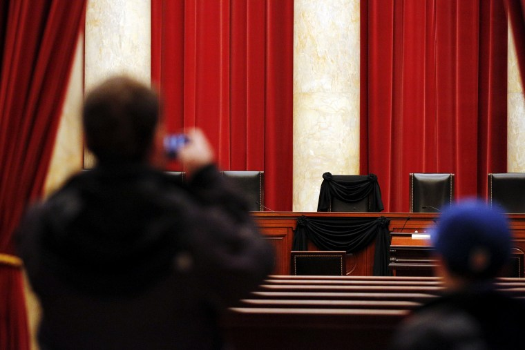 A visitor takes a picture of the bench of late Supreme Court Justice Antonin Scalia, draped with black wool crepe, inside the Supreme Court in Washington, Feb. 16, 2016. (Photo by Carlos Barria/Reuters)