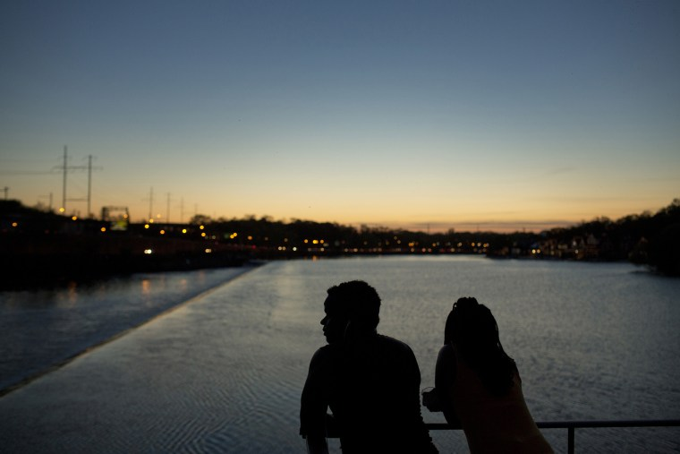 The silhouettes of people are seen watching the sunset over the Schuylkill River in Philadelphia, May 8, 2015. Philadelphia. (Photo by Victor J. Blue/Bloomberg/Getty)
