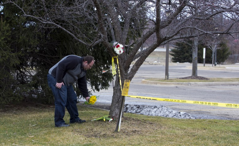 A man places flowers at a Cracker Barrel where a gunman went on a shooting rampage, on Feb. 21, 2016 in Kalamazoo, Mich. (Photo by Tasos Katopodis/Getty)