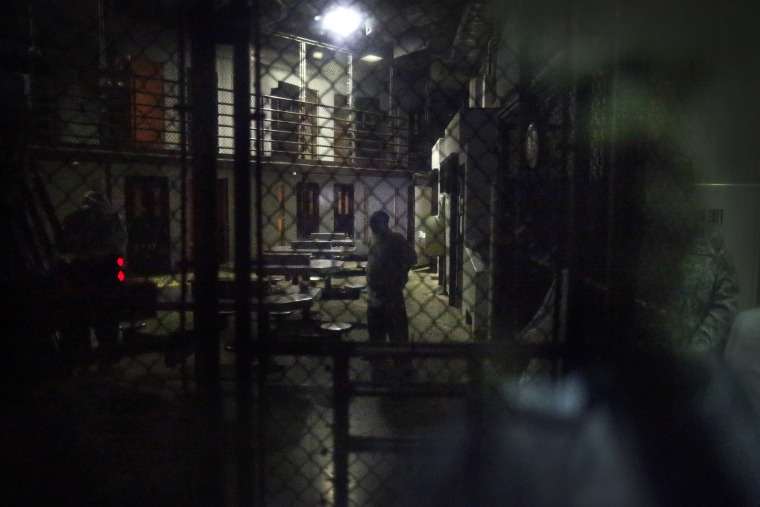 In this photo reviewed by the U.S. military, detainees behind a mirrored one-way window are pictured in Camp VI detention facility at Guantanamo Bay Naval Base, Cuba, Nov. 20, 2013. (Photo by Charles Dharapak/AP)
