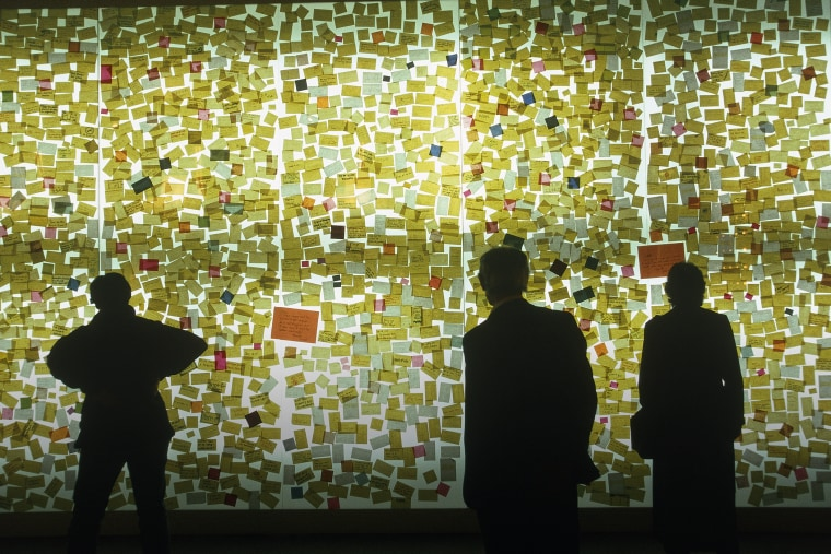 Curious visitors read sticky notes on a wall. (Photo by Construction Photography/Corbis)